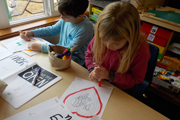 School age child drawing heart
