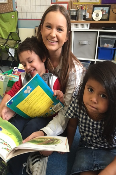 Univsersity student reading to children